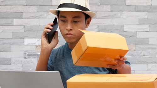 business owner talking on the phone and holding a box