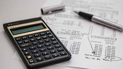 a focused image of a calculator with a pen and account statement on the background