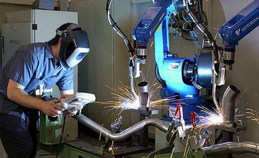 Employee adjusting the welding robot arm
