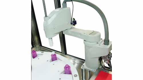 A SCARA robot being dispensing bottle tops