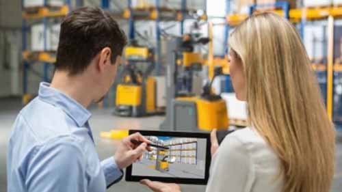 Two people looking at a tablet in a warehouse